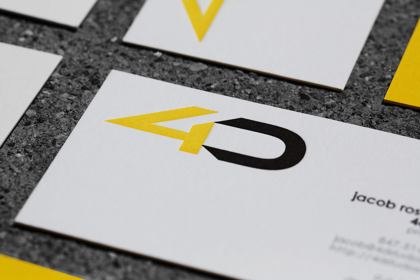 a grouping of 4D letterpress business cards, featuring some right side up, with others upside down